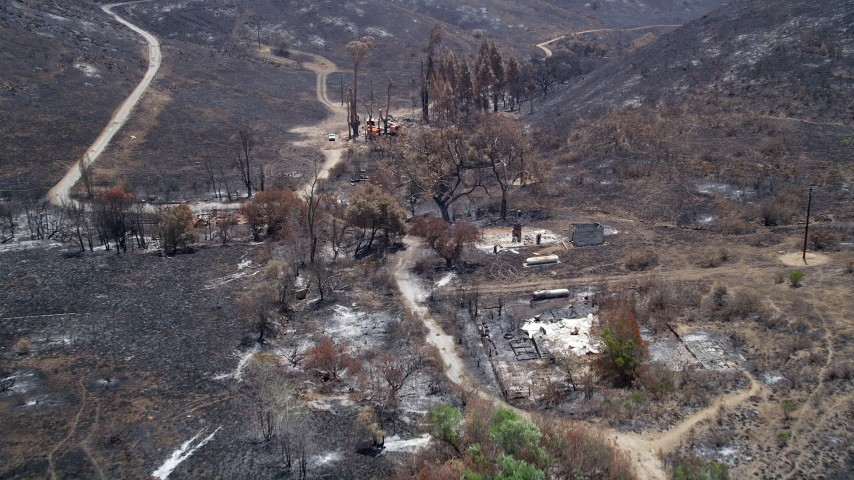 5K stock footage aerial video approach and fly over rural homes destroyed by wildfires in Santa Monica Mountains, California Aerial Stock Footage | AX42_015