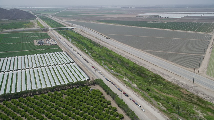 5K stock footage aerial video flyby cars on a dirt road by crop fields, greenhouses, and South Lewis Road, Camarillo, California Aerial Stock Footage | AX42_024