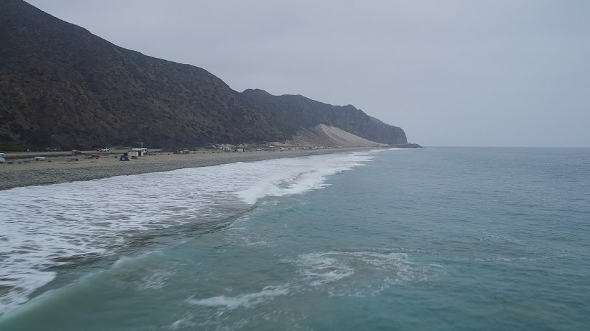 5K aerial video of flying low over Pacific Ocean waves rolling in toward a beach, Malibu, California Aerial Stock Footage AX42_064