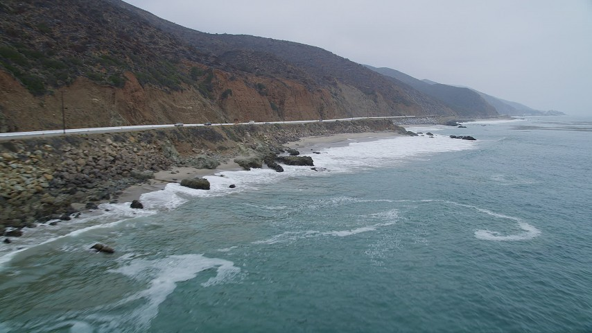 Fly low over ocean waves beside Highway 1 with light traffic, Malibu, California Aerial Stock Footage | AX42_072