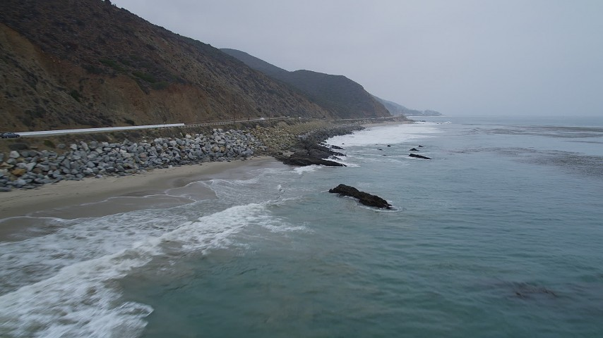 5K stock footage aerial video of flying low over waves rolling toward the coast and Highway 1, Malibu, California Aerial Stock Footage | AX42_073