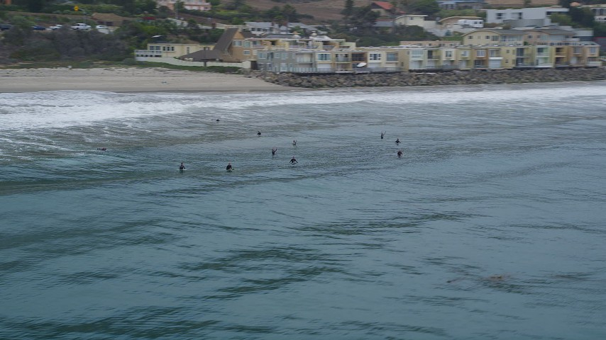 5K stock footage aerial video track a group of surfers in the ocean near a beach, Malibu, California Aerial Stock Footage | AX42_079