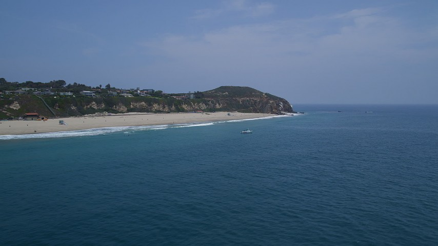 5K aerial video of a sparsely populated beach and Point Dume, seen from the ocean, Malibu, California Aerial Stock Footage | AX42_086