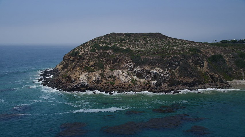 Blue waters at the bottom of the cliffs of Point Dume, Malibu, California Aerial Stock Footage | AX42_089