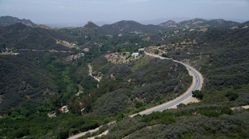 Fly over Kanan Dume Road to approach hillside mansions in the hills, Malibu, California Aerial Stock Footage | AX42_098