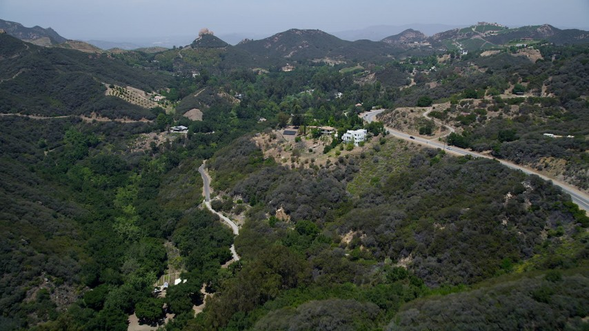 5K stock footage aerial video fly over Kanan Dume Road to approach hillside mansions in Malibu, California Aerial Stock Footage | AX42_098