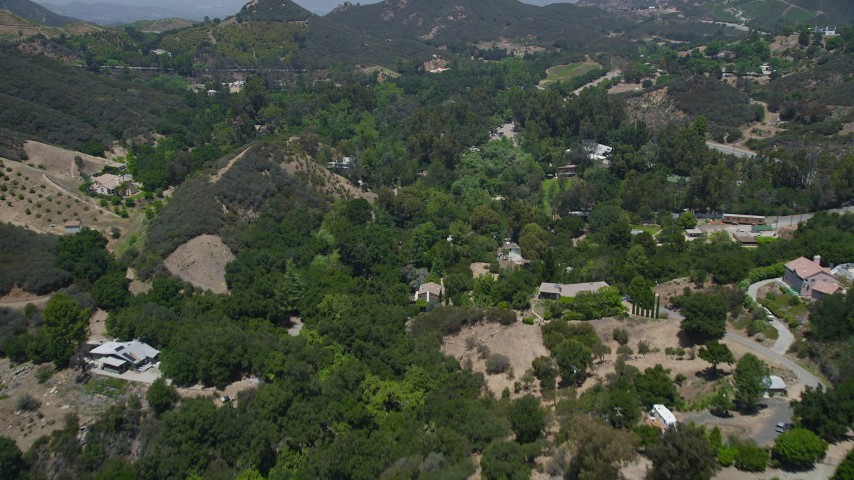 Flying over mansions and small hills, Malibu, California Aerial Stock Footage | AX42_099