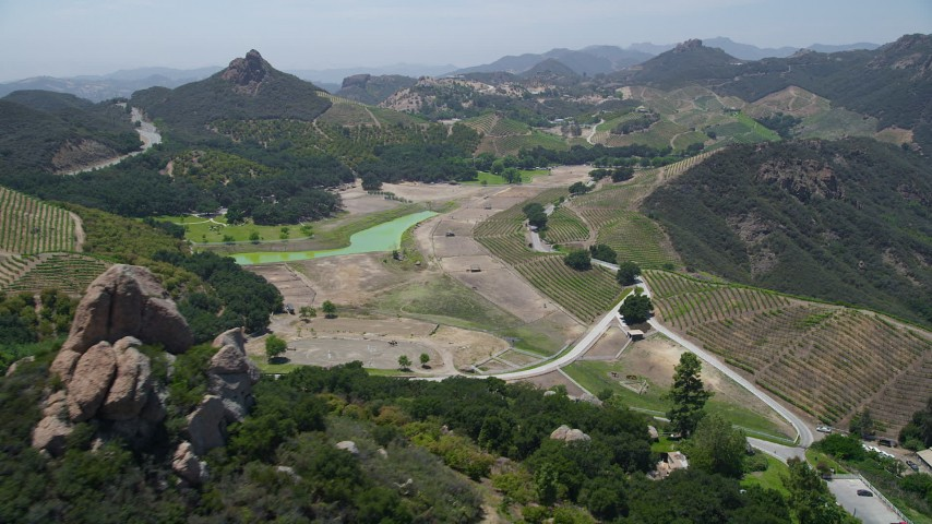 5K aerial video flyby rock formations atop hills, vineyards, and a country road in Malibu, California Aerial Stock Footage | AX42_101