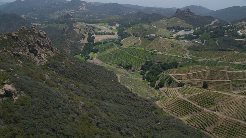 5K stock footage aerial video approach and fly over rock formations to reveal hilly vineyards, Malibu, California Aerial Stock Footage | AX42_104