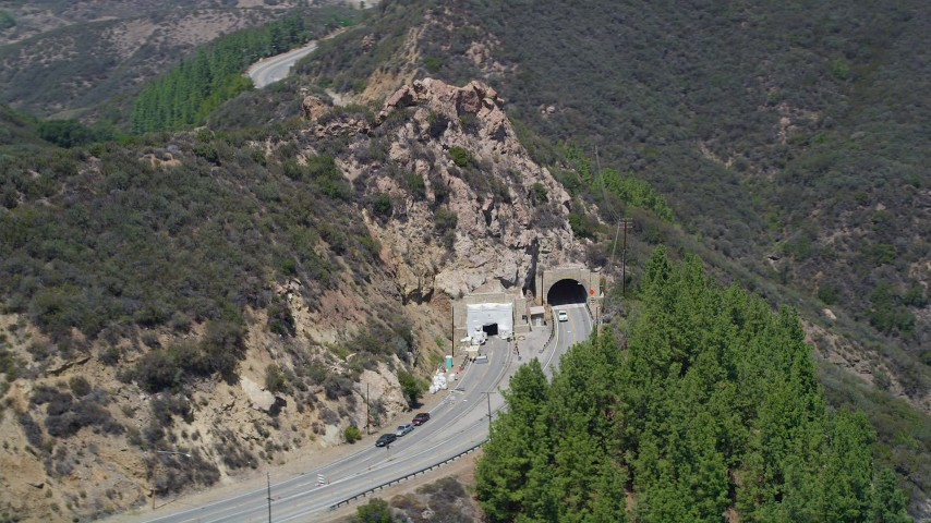 Flying by a tunnel through a hill on Kanan Road, Malibu, California Aerial Stock Footage | AX42_110