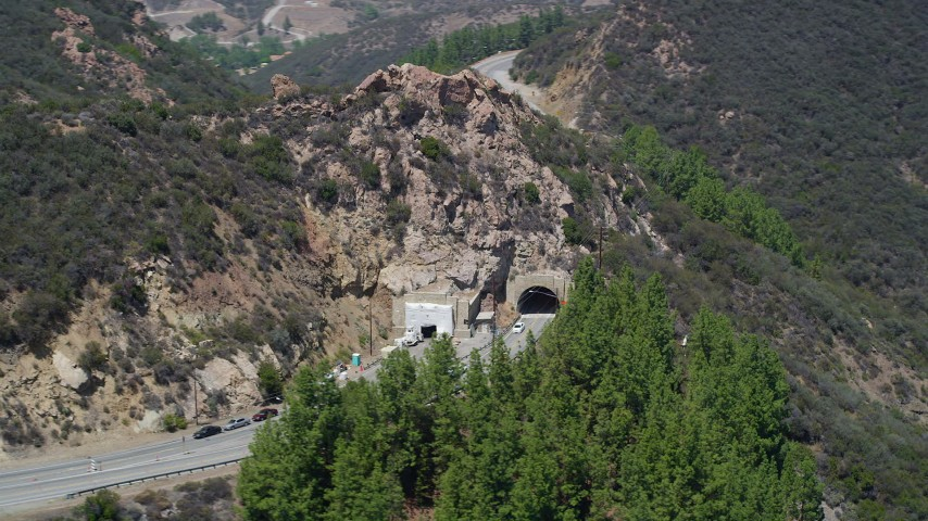 5K stock footage aerial video of flying by a tunnel through a hill on Kanan Road, Malibu, California Aerial Stock Footage | AX42_110