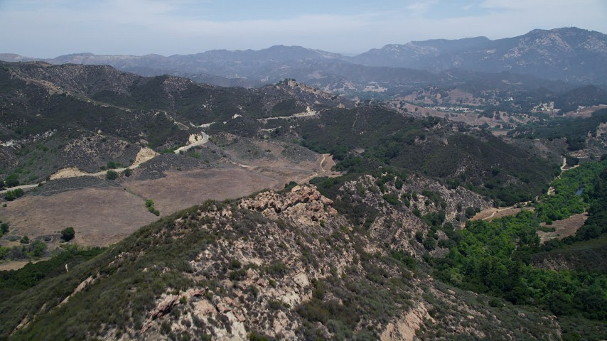 5K stock footage aerial video fly over Santa Monica Mountains to approach Mulholland Highway, California Aerial Stock Footage | AX42_115