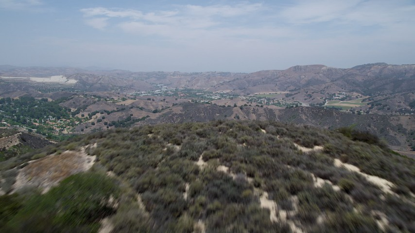 5K aerial video of flying low over Santa Monica Mountains to reveal Calabasas, California Aerial Stock Footage | AX42_117