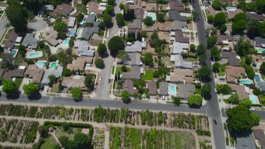 5K stock footage aerial video of reverse view of suburban homes, school, a nursery, and apartment buildings, Canoga Park, California Aerial Stock Footage | AX42_120