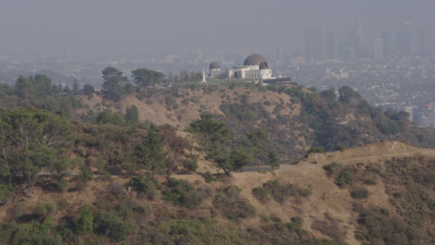 4K stock footage aerial video of the Griffith Observatory seen while descending behind trees, Los Angeles Aerial Stock Footage | AX43_016