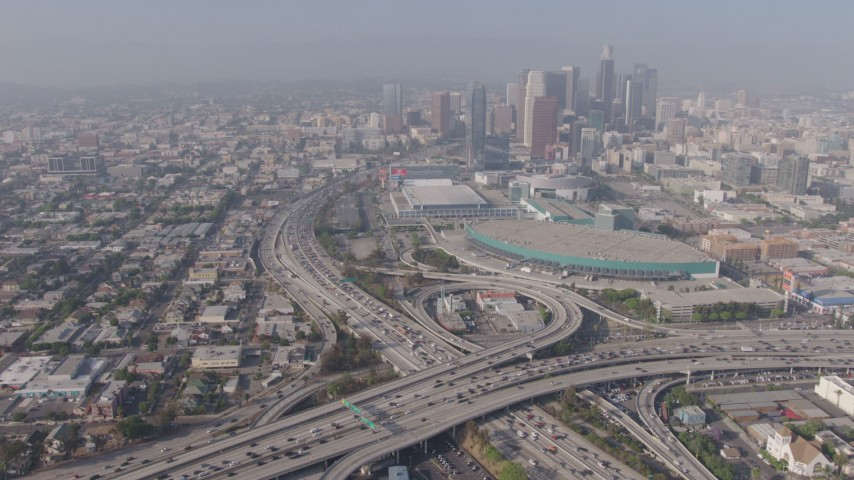 4K stock footage aerial video orbiting heavy traffic in the 110/10 interchange, and tilt to reveal the Los Angeles Convention Center and skyscrapers, Downtown Los Angeles, California Aerial Stock Footage | AX43_021