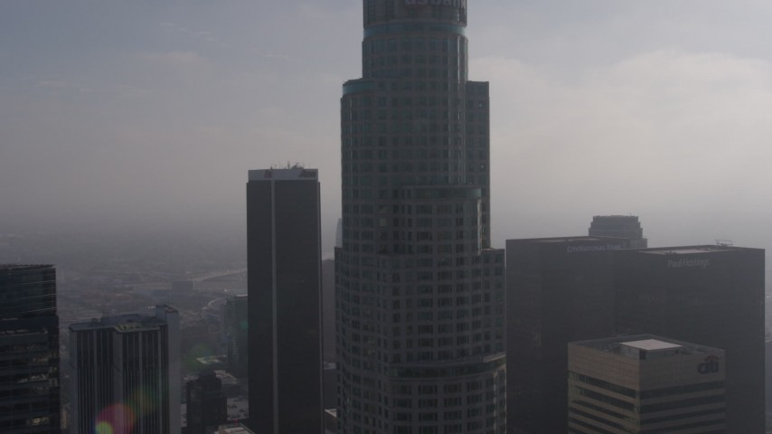 4K stock footage aerial video flying by US Bank Tower, and over City National Plaza and Paul Hastings  Tower on a foggy day, Downtown Los Angeles, California Aerial Stock Footage | AX43_027