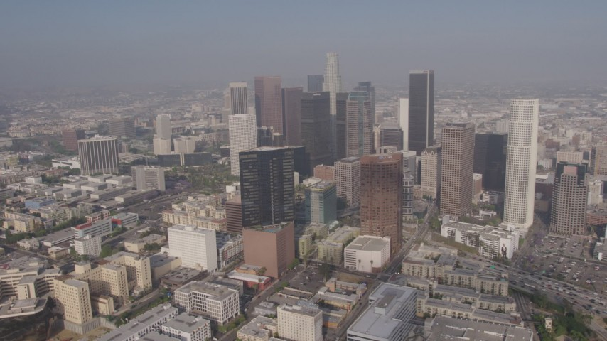 4K stock footage aerial video flying by Downtown Los Angeles skyscrapers seen from north of the city, California Aerial Stock Footage | AX43_030