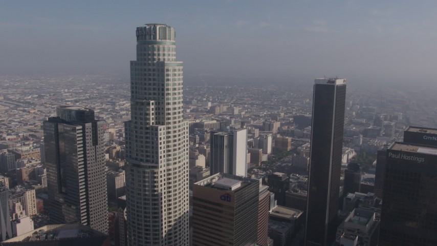 4K stock footage aerial video flying between US Bank Tower and Aon Center to focus on city sprawl in the background, Downtown Los Angeles, California Aerial Stock Footage | AX43_033