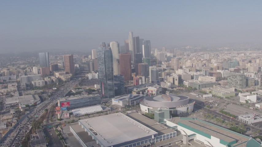 4K stock footage aerial video tilting from heavy rush hour traffic on I-110 to reveal Staples Center, Ritz-Carlton and Downtown Los Angeles skyscrapers in California Aerial Stock Footage | AX43_034