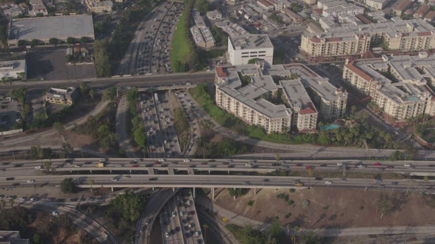 4K stock footage aerial video of bird's eye of traffic on the I-110 / 101 interchange, panning to apartment buildings, Downtown Los Angeles, California Aerial Stock Footage | AX43_042