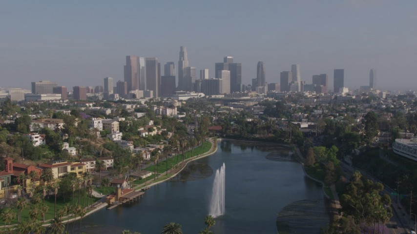 4K aerial video flying over Echo Park Lake fountain to approach Downtown Los Angeles skyline, California Aerial Stock Footage AX43_043