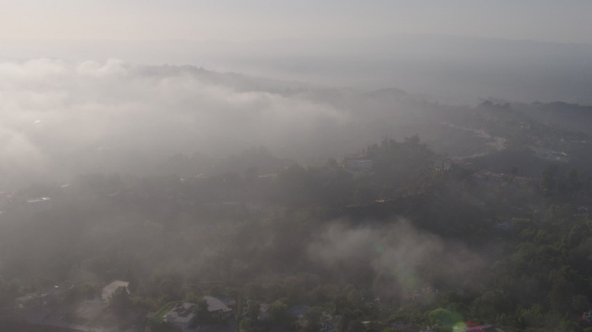 4K stock footage aerial video approaching the marine layer rolling over upscale, hillside homes in Beverly Hills, California Aerial Stock Footage | AX43_060
