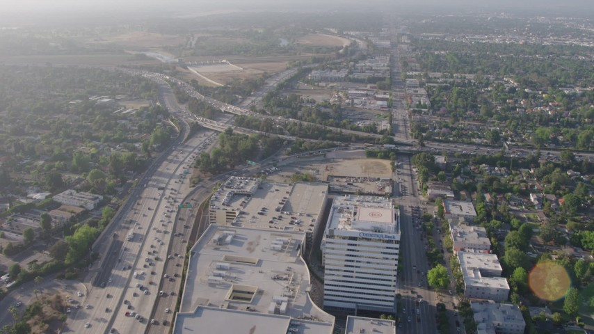 4K aerial video flying over office buildings and the Sherman Oaks Galleria to approach heavy traffic on the I-405 and 101 interchange, Sherman Oaks, California Aerial Stock Footage | AX43_063