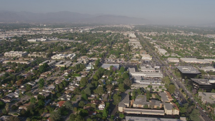 4K stock footage aerial video flying by suburban neighborhoods, busy city streets, and office buildings, Van Nuys, California Aerial Stock Footage | AX43_067