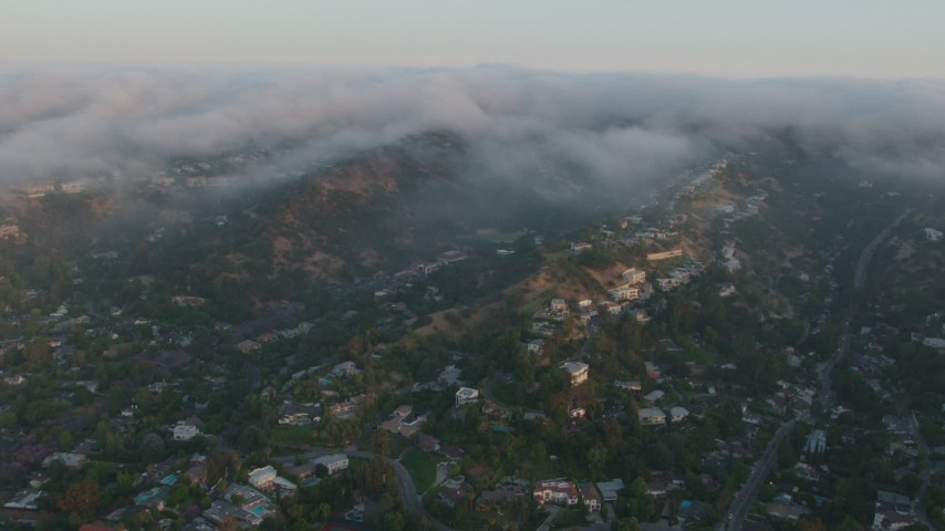 4K stock footage aerial video of upscale hillside homes with fog rolling over the hills, Sherman Oaks, California, sunset Aerial Stock Footage | AX44_003