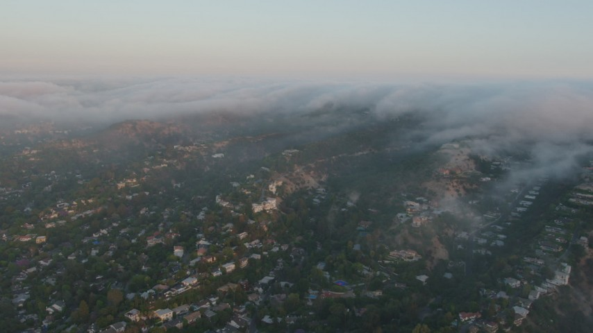 4K stock footage aerial video of Hillside homes with fog rolling over the tops of hills, Sherman Oaks, California, sunset Aerial Stock Footage | AX44_004