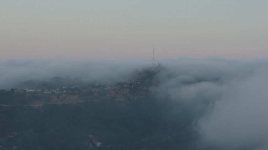 4K stock footage aerial video of a radio tower peaking out from marine layer, Hollywood Hills, California, sunset Aerial Stock Footage | AX44_016