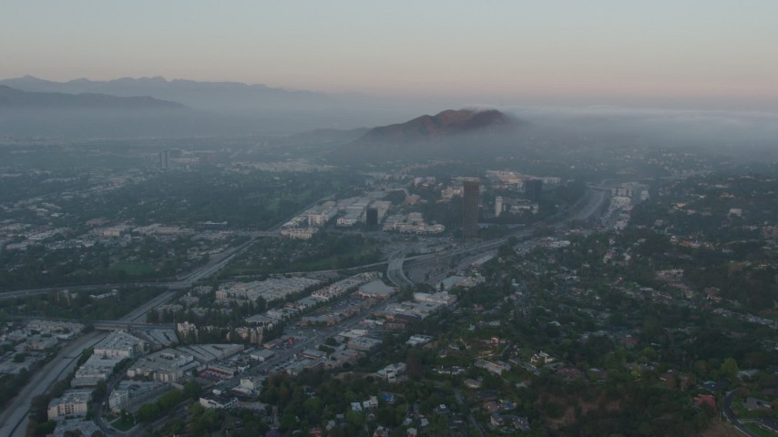 4K stock footage aerial video of fog rolling near Universal City, Universal Studios, California, sunset Aerial Stock Footage | AX44_017