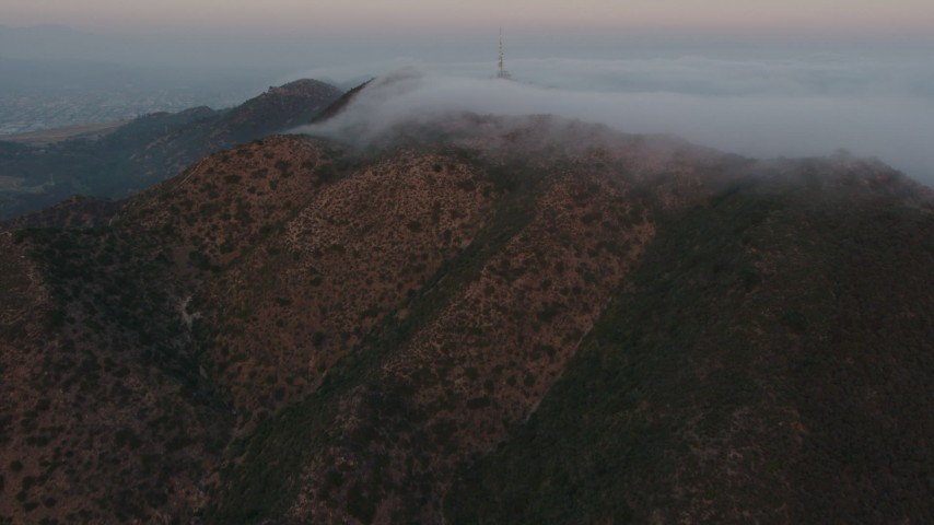 4K stock footage aerial video of the Marine Layer rolling over Hollywood Hills, Los Angeles, California, sunset Aerial Stock Footage | AX44_020