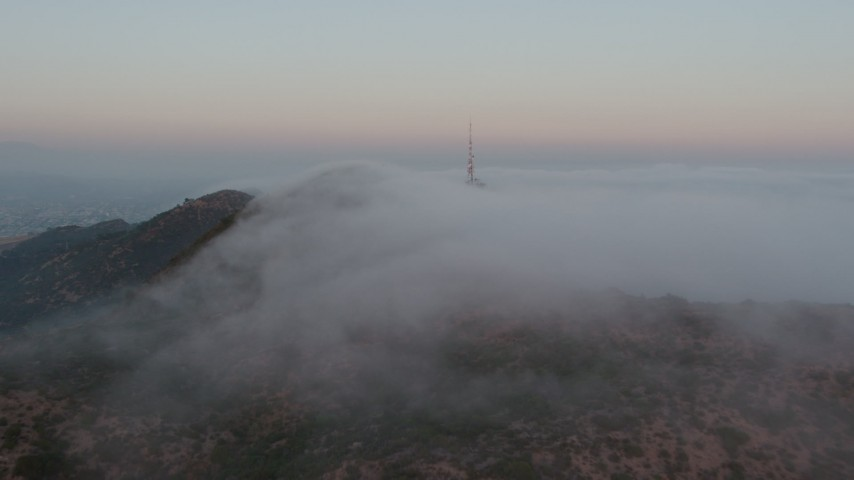 4K stock footage aerial video of the marine layer rolling over Hollywood Hills toward radio tower, California, sunset Aerial Stock Footage | AX44_021