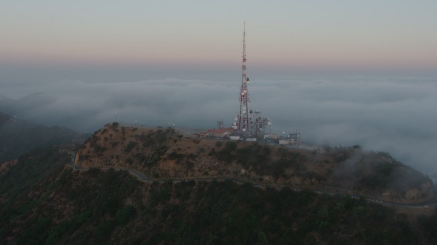 4K stock footage aerial video of a radio tower atop Hollywood Hills near marine layer, California, sunset Aerial Stock Footage | AX44_022