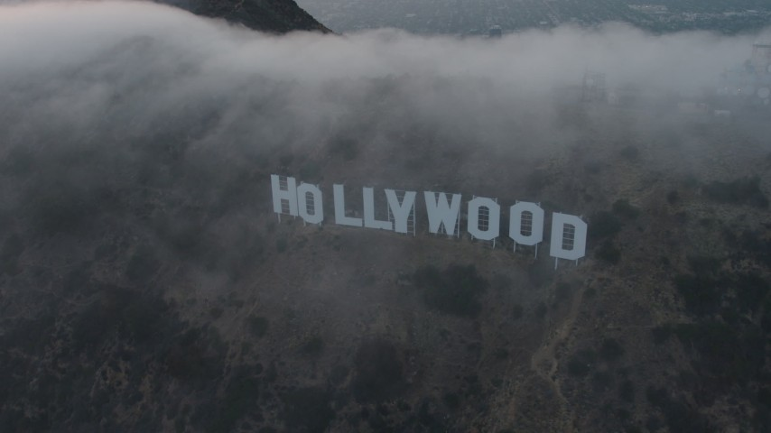 4K stock footage aerial video orbiting Hollywood Sign covered in marine layer, California, sunset Aerial Stock Footage | AX44_028