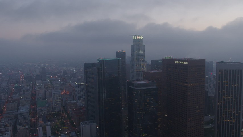 4K stock footage aerial video orbiting skyscrapers and high-rises below marine layer, Downtown Los Angeles, twilight Aerial Stock Footage | AX44_050