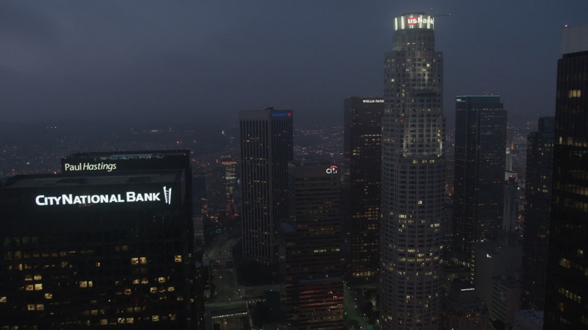 4K aerial video tilting up from city streets revealing skyscrapers, Downtown Los Angeles, night Aerial Stock Footage | AX44_065