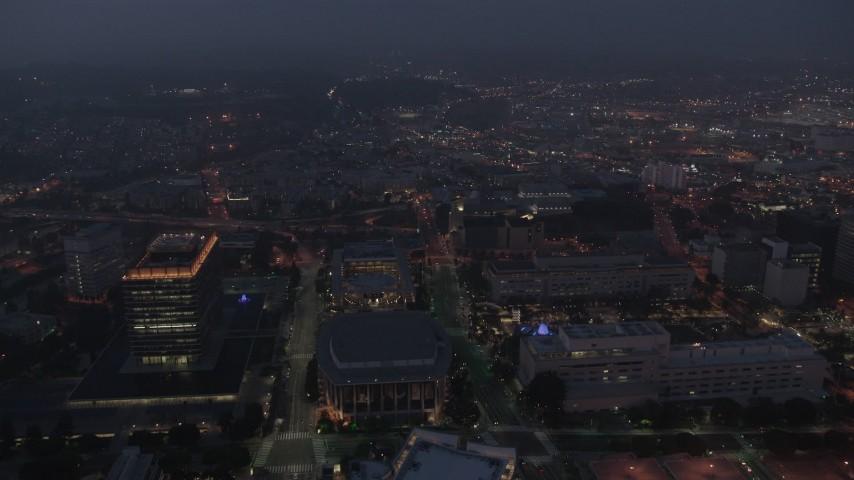 4K aerial video flying by skyscrapers revealing Walt Disney Concert Hall, Los Angeles, night Aerial Stock Footage | AX44_066