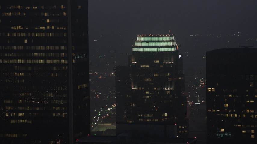 4K stock footage aerial video flying by Figueroa at Wilshire skyscraper, Downtown Los Angeles, night Aerial Stock Footage | AX44_075