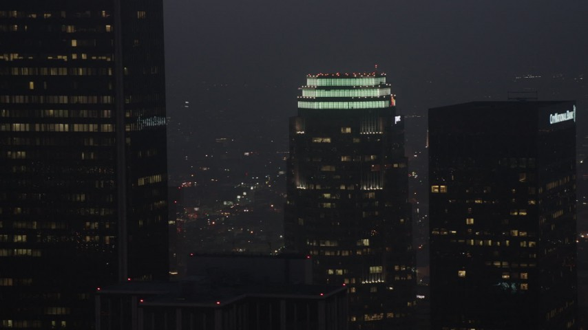 4K aerial video of a medium shot flying by skyscrapers, Downtown Los Angeles, night Aerial Stock Footage | AX44_076
