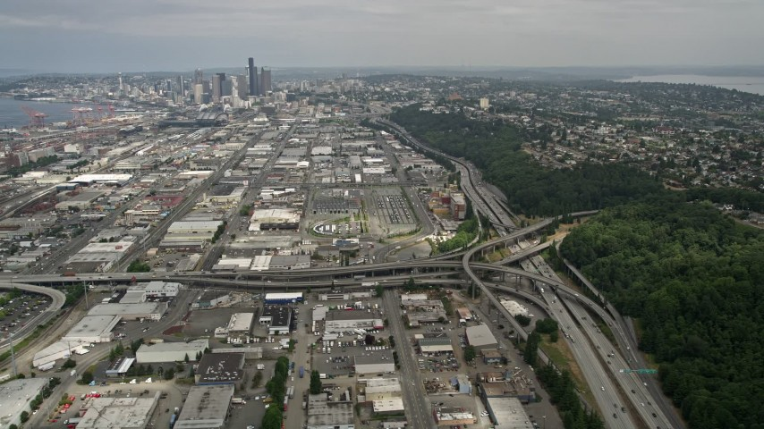 5K stock footage aerial video tilting from Interstate 5 to reveal warehouse buildings and Downtown Seattle, Washington Aerial Stock Footage   AX45_014
