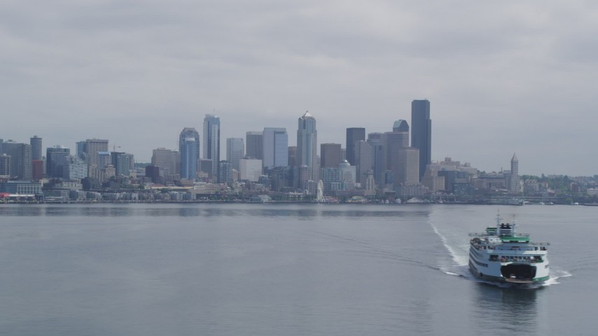 5K stock footage aerial video passing a ferry sailing away from Downtown Seattle, Washington Aerial Stock Footage | AX45_027