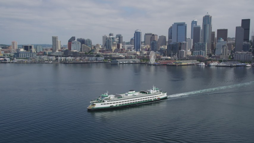 5K stock footage aerial video tracking a ferry sailing away from Downtown Seattle skyline, Washington Aerial Stock Footage | AX45_042