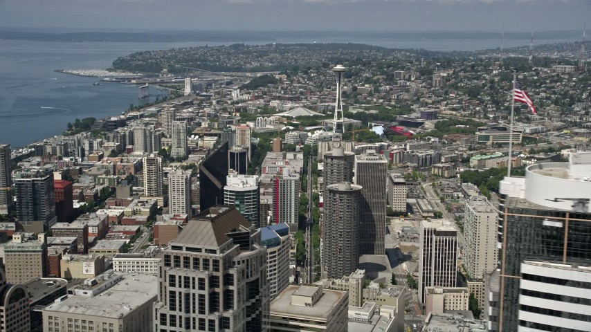 5K stock footage aerial video of the Space Needle seen while flying by downtown skyscrapers, Downtown Seattle, Washington Aerial Stock Footage | AX45_052