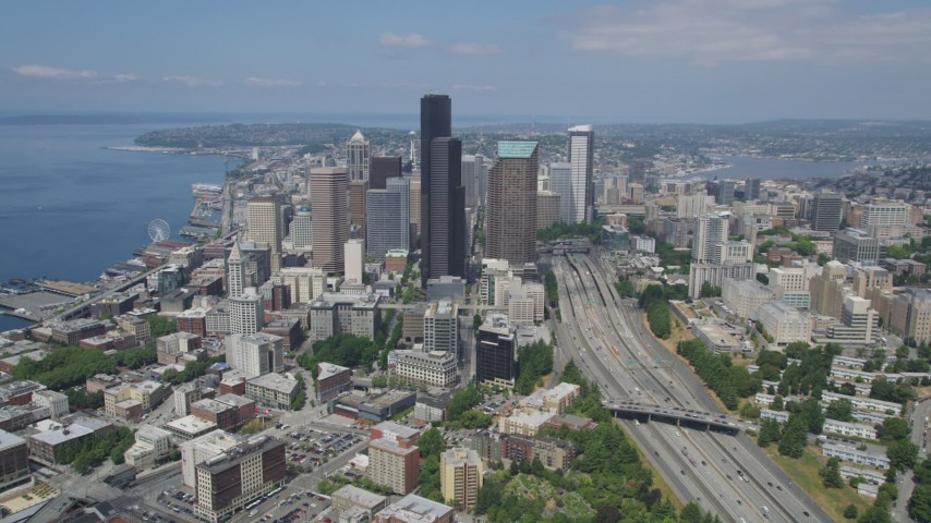 5K stock footage aerial video tilting from light traffic on the I-5 Express to reveal skyscrapers in Downtown Seattle, Washington Aerial Stock Footage | AX45_064