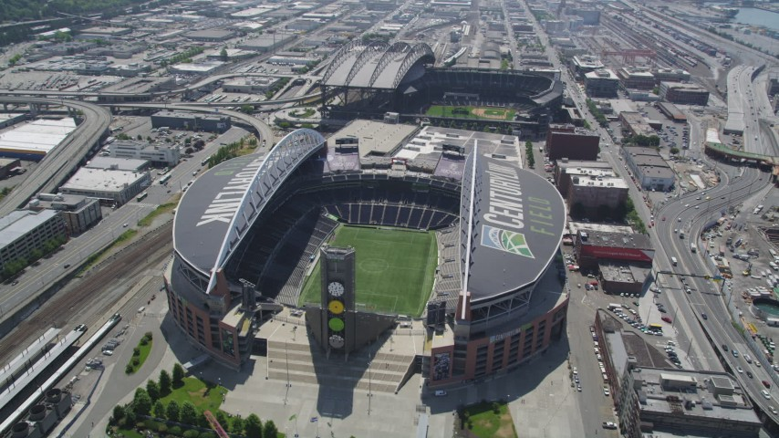5K stock footage aerial video flying by CenturyLink Field, with a view of the field inside the stadium, Downtown Seattle, Washington Aerial Stock Footage AX45_091 | Axiom Images