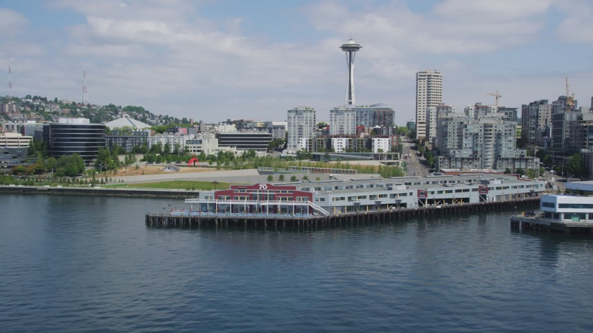 5K stock footage aerial video flying by Pier 70 with the Space Needle in the background, reveal modern waterfront office buildings, Downtown Seattle, Washington Aerial Stock Footage | AX45_100