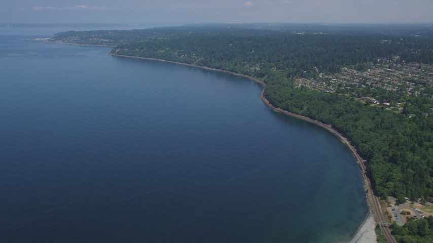 5K stock footage aerial video fly over Puget Sound to approach railroad tracks on the shore by Broadview, Washington Aerial Stock Footage AX45_114 | Axiom Images